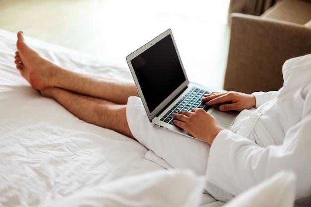 ローブを着た男がベッドに横になり、コンピューターを足元に置いて自宅でフリーランスの仕事をしている男は顔を出さない...