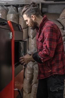 Мужчина в комнате с твердотопливным котлом, работает на биотопливе, экономное отопление.