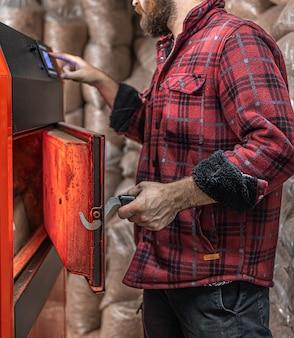 固形燃料ボイラーのある部屋で、バイオ燃料、経済的な暖房に取り組んでいる男性。