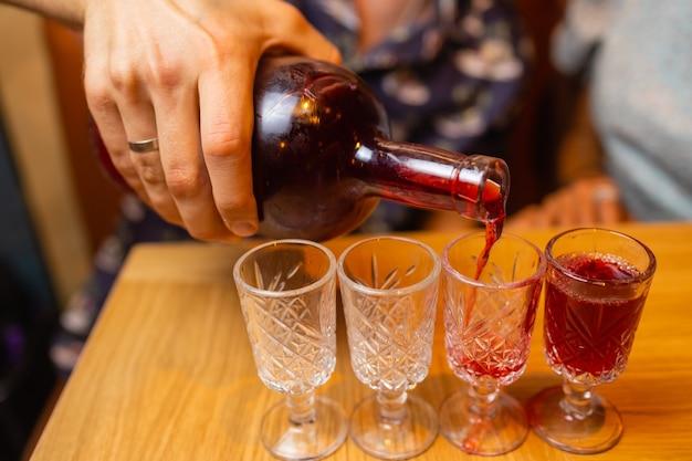 素朴なシャツを着た男がグラスにウイスキーを注ぐウイスキーはアルコール飲料を飲む