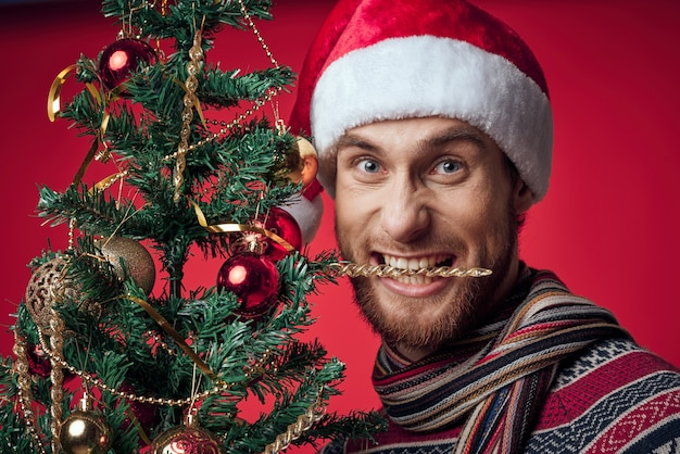 サンタの帽子の男クリスマスツリーの装飾おもちゃ赤い背景。高品質の写真