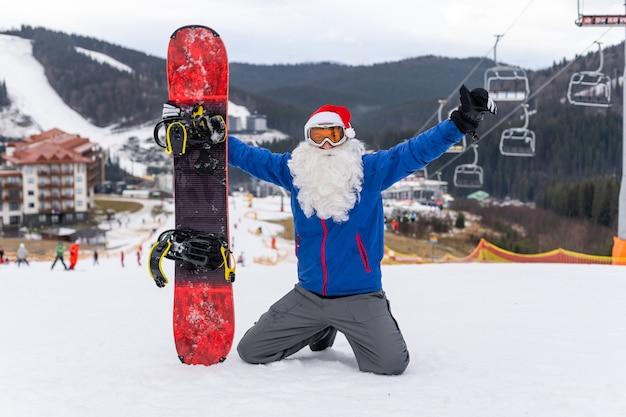 スキーリゾートでスノーボードを持ったサンタの帽子をかぶった男。