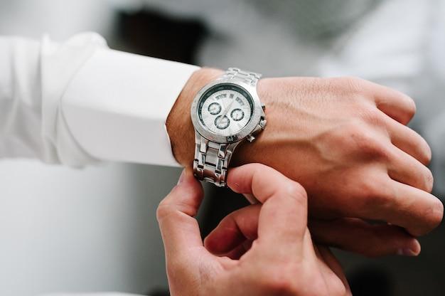 셔츠를 입은 남자가 팔에 시계를 조정합니다. 시계를 사용하는 사업가의 닫습니다.