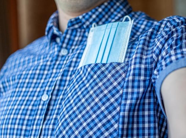 셔츠를 입은 남자와 주머니에 covid-19의 의료용 마스크. covid-19, 코로나바이러스 이후의 새로운 정상에서 관광 및 여행의 개념. 전염병 동안 도시와 사회의 삶