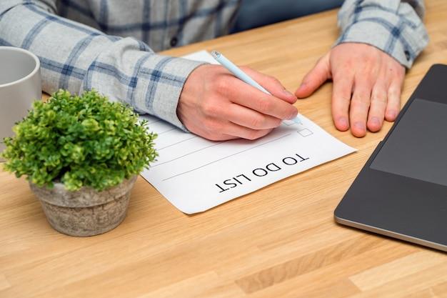 シャツを着た男性が、木製のテーブルに座ってチェックボックス付きの「todoリスト」のユニフォームを完成させました