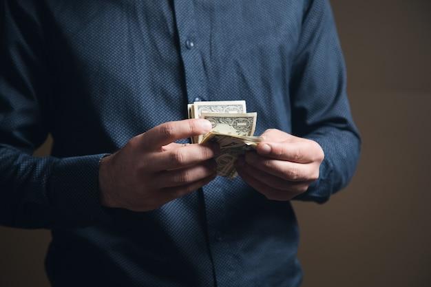 셔츠를 입은 남자가 갈색 표면에 돈을 세고 있습니다.
