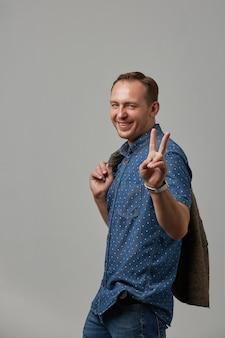 Мужчина в рубашке показывает руками жест победы