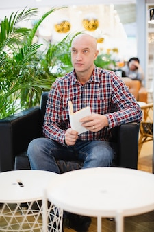 Мужчина в рубашке сидит в кресле в квартире и читает книгу