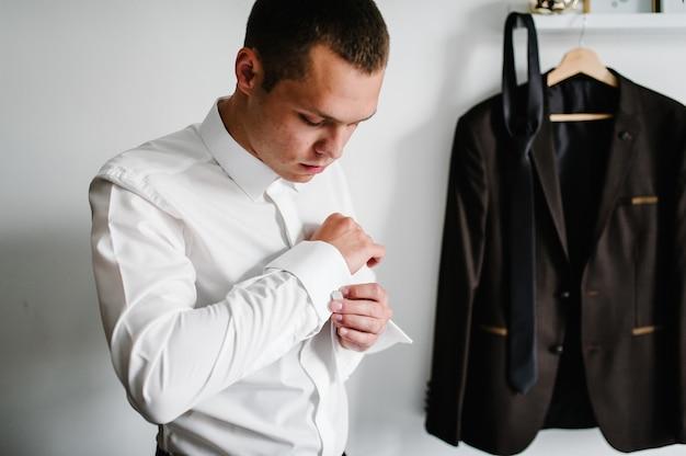 シャツを着た男性は、腕にメタリックシルバーのカフスボタンを着用しています。白い壁にネクタイがぶら下がっている茶色のジャケットの背景に。手の新郎。結婚式の日。