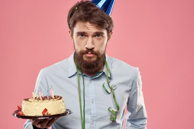 ケーキを手に、お祝いの帽子を頭にかぶったシャツを着た男性。高品質の写真