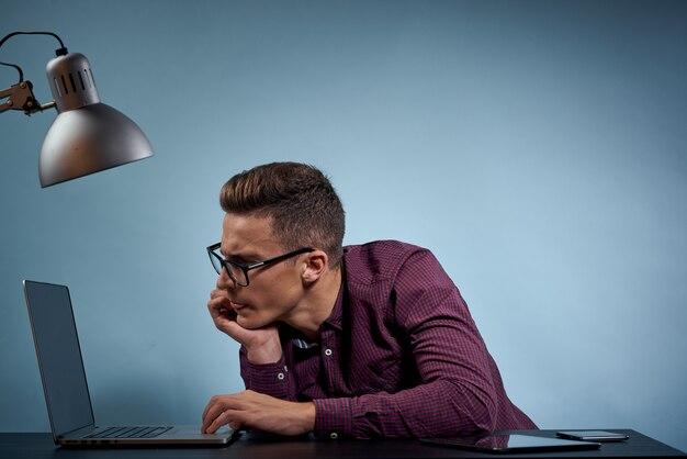 Мужчина в рубашке с ноутбуком за столом - менеджер в офисе и модель лампового шкафа.