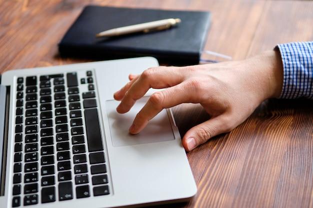 Человек в рубашке работает за ноутбуком, ведя рукой на сенсорной панели.