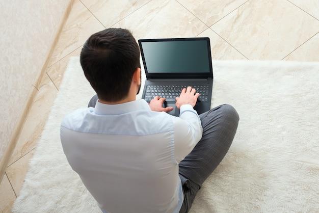シャツを着た男性が自宅のノートパソコンを遠くに座って仕事をしている