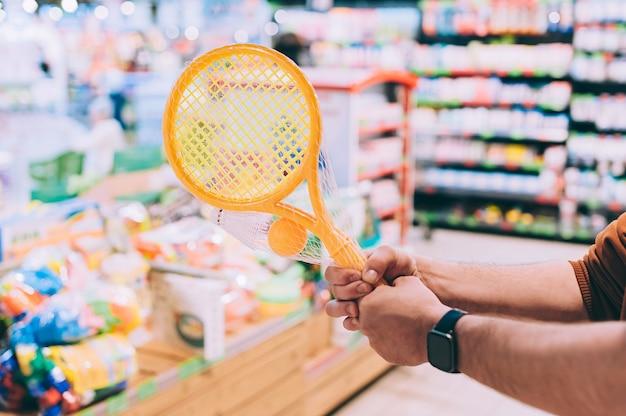 가게의 한 남자가 어린 이용 테니스 세트를 선택하고 테니스 라켓을 손에 들고 있습니다.
