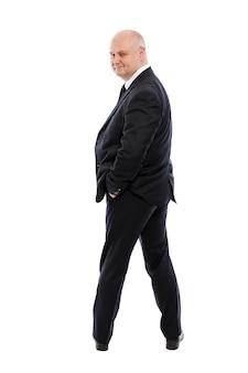 厳格な黒のスーツを着た男はずる賢く微笑む。背面図。孤立