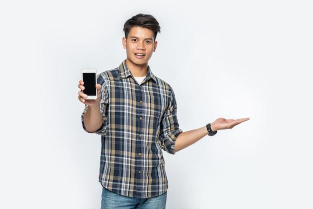 縞模様のシャツを着た男性が左手を開き、スマートフォンを持っています