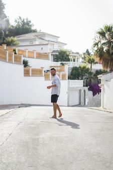 ストライプのシャツを着た男が、スペインの小さな町の通りを歩いています。