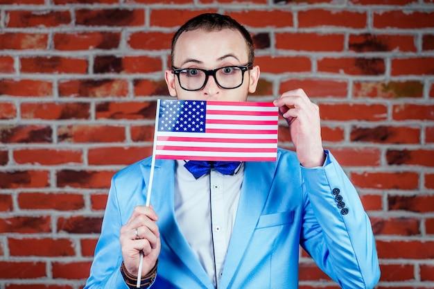 Мужчина в стильном костюме держит в руке флаг америки. концепция празднования дня независимости 4 июля