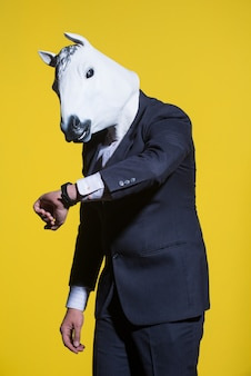 양복을 입은 남자와 그의 시계를 보고 있는 말 마스크 개념적 사업 배경