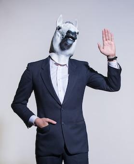 スーツを着た男と明るい背景の馬マスク。概念的なビジネスの背景