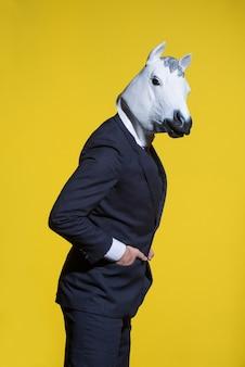 Мужчина в костюме и маске лошади на желтом фоне. концептуальный бизнес фон