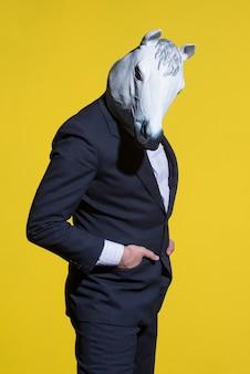 노란색 배경에 양복과 말 마스크를 쓴 남자. 개념적 사업 배경