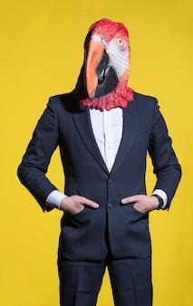 スーツを着た男とオウムのマスク。概念的なビジネスの背景
