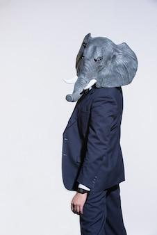 スーツを着た男と明るい背景の象のマスク。概念的なビジネスの背景