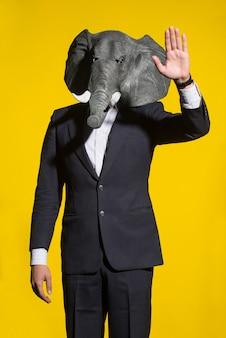 スーツを着た男と黄色の背景に象のマスク。概念的なビジネスの背景