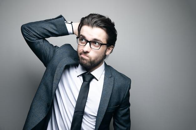 Мужчина в костюме и очках задумчиво выглядит, чешет затылок на серой стене