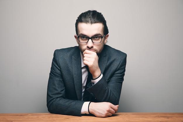 スーツと眼鏡をかけた男が座って灰色の壁を見る