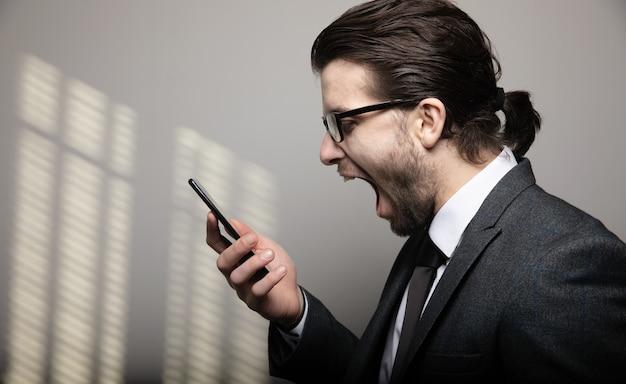 양복과 안경을 입은 남자가 회색 벽에 전화로 소리 지른다.