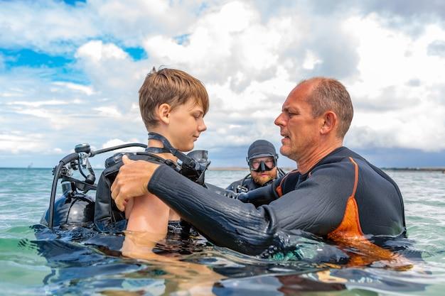ダイビングのスーツを着た男性が男の子にダイビングの準備をさせる
