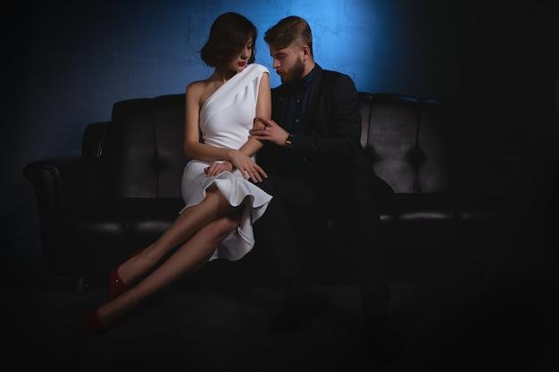 スーツを着た男性がソファーに座っている若いブロンドの女性を優しく抱きしめる