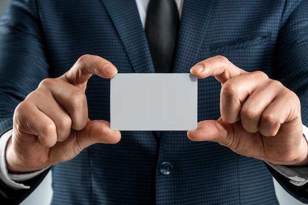 Мужчина в костюме руки крупным планом показывает визитную карточку. макет, верстка.