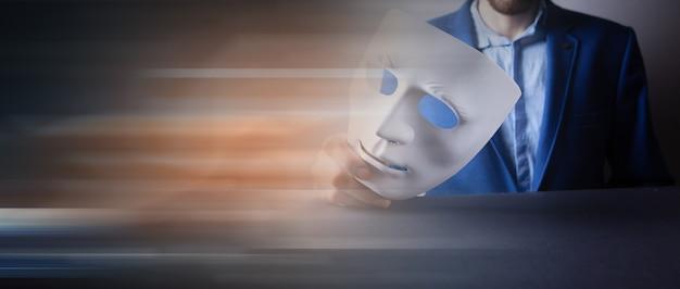 匿名のマスクを持っているスーツを着た男