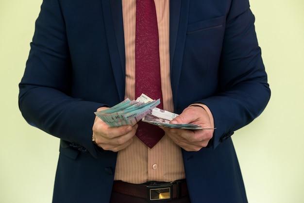 スーツを着た男性がウクライナのお金を大量に持っており、収入を示しています。 uah。新しい紙幣1000および500グリブナ