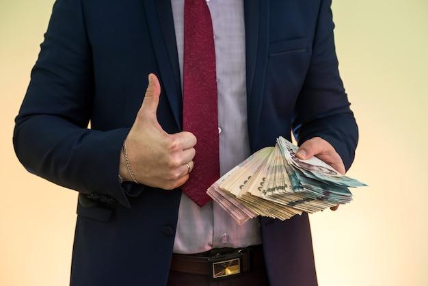 양복을 입은 한 남자가 우크라이나 돈을 많이 들고 수입을 보여줍니다. uah. 새 지폐 1000 및 500 흐 리브 냐