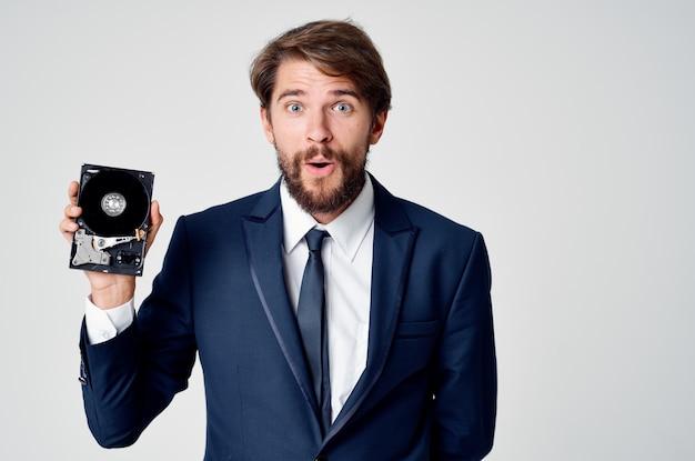 スーツを着た男は彼の手と灰色の背景に組み立てられていないハードドライブを持っています