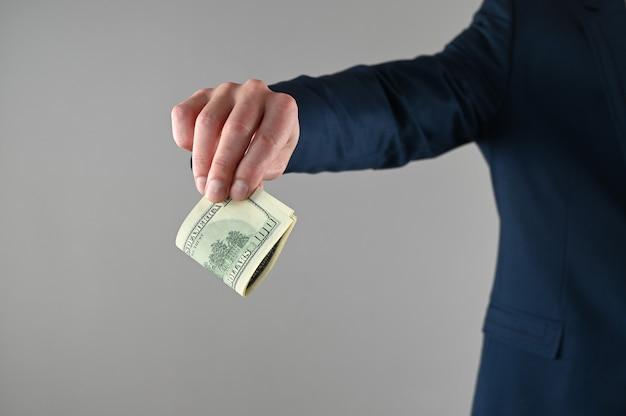 양복 입은 남자가 돈을 손에 쥐고있다.