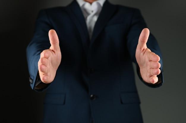 Мужчина в костюме имитирует держащийся предмет. мужчина в костюме разводит руками по черному пространству. концепция: положительное сообщение в бизнесе.