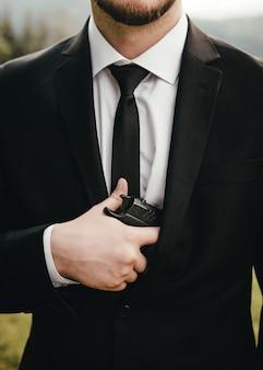 Мужчина в костюме, пиджаке и белой рубашке, с черным галстуком, держит в руке пистолет.