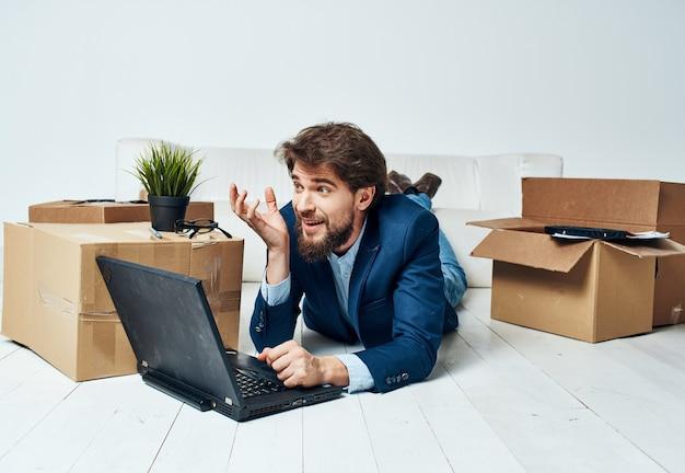Мужчина в костюме лежит на полу с офисными коробками, распаковывая ноутбук.