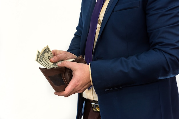 スーツを着た男が財布を見て、たったの1ドルを引き出します。台無しにされたビジネスマン。失敗または破産の概念
