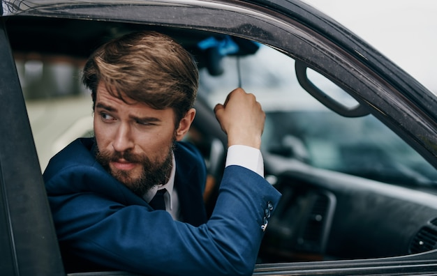 スーツを着た男が窓の外を見る車に乗る楽しいライフスタイル