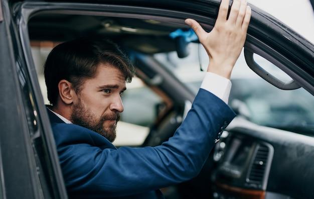 スーツを着た男性が窓の外を眺める車に乗って楽しいライフスタイル。