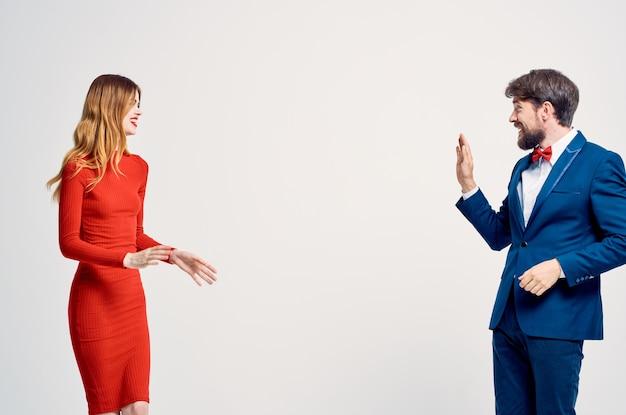 赤いドレスのコミュニケーションファッション孤立した背景の女性の隣にスーツを着た男性