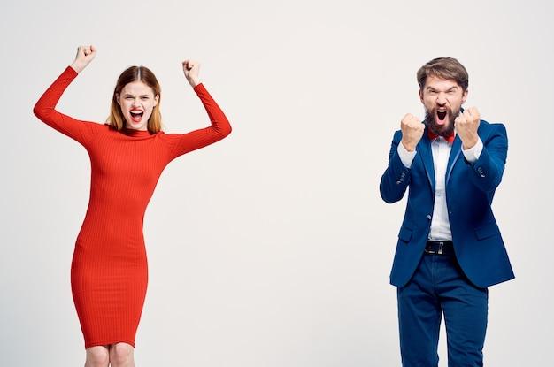 Мужчина в костюме рядом с женщиной в красном платье, эмоции, жесты рук, изолированный фон