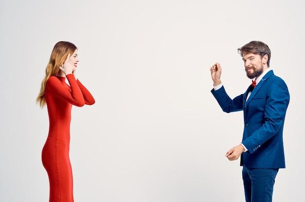 赤いドレスのロマンス幸せな孤立した背景の女性の隣にスーツを着た男性。高品質の写真