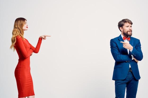 赤いドレスのロマンス幸せな光の背景の女性の隣にスーツを着た男性